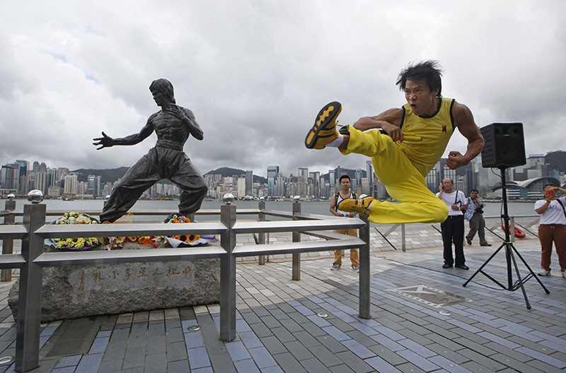 Китайский актер Мэй Чжиен выступает перед бронзовой статуей в Гонконге
